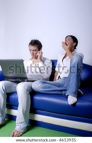 Young couple sitting in a sofa using a laptop
