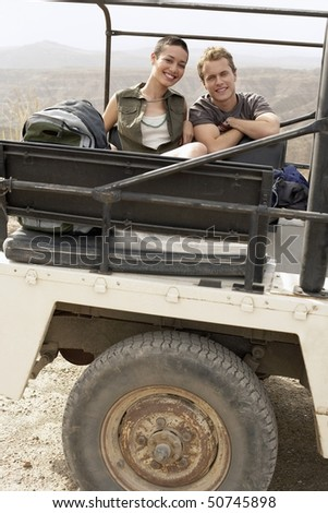 Young couple sitting in back of four wheel drive car in desert, portrait