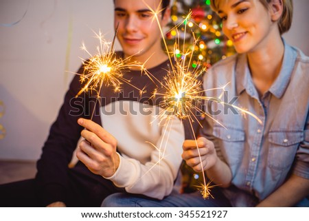 Young couple sitting in front of Christmas tree and holding sparklers #345521927