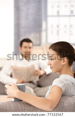 Young couple sitting in living room on sofa, man reading newspaper, woman drinking tea, smiling in front.?