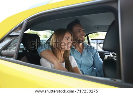 Young couple sitting in taxi car