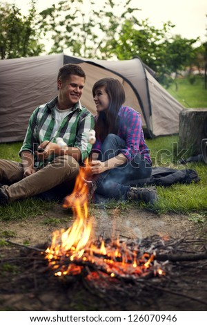 Young couple sitting near a campfire and toasting marshmallow