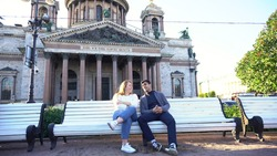 Young couple sitting on a bench near Saint Isaac Cathedral in Saint Petersburg, Russia. Media. Man and woman sitting together and chatting as friends.