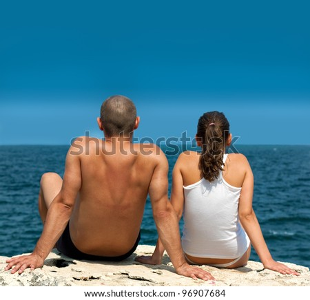 Young couple sitting on a cliff and looking at sea or ocean.Copy space