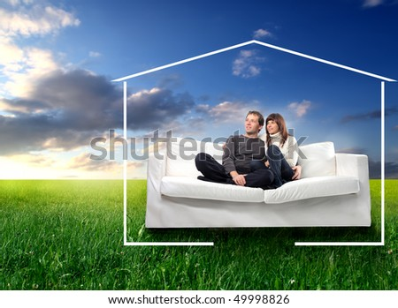 Young couple sitting on a couch on a green meadow surrounded by the form of a house