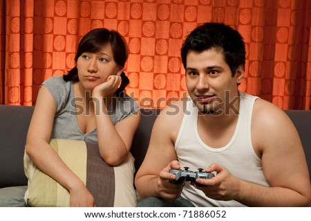 young couple sitting on a couch. The guy is playing video games, while the girl is bored