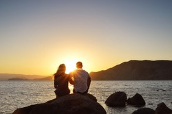 Young couple sitting on a rock near the sea and watching the sun