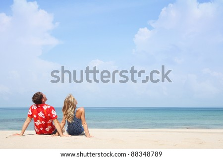 Young couple sitting on a sand and looking to a tropical cloudy sky