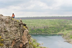 Young couple sitting on a steep rocky cliff top overlooking a scenic valley with a wide river below as they enjoy a refreshing healthy day outdoors in nature