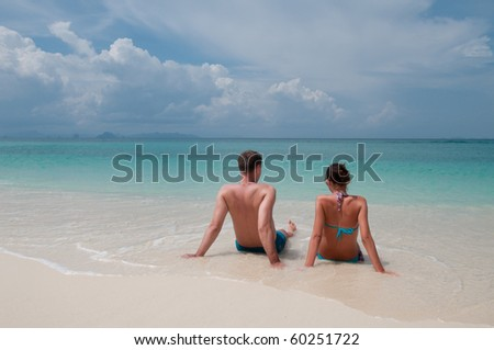Young couple sitting on a tropical beach