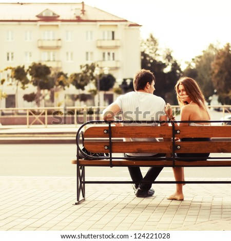 Young couple sitting on bench in park. Rear view.