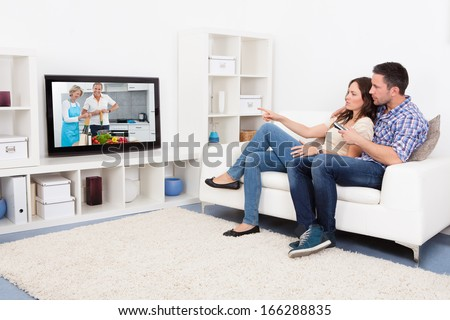 Young Couple Sitting On Couch Watching Cookery Show
