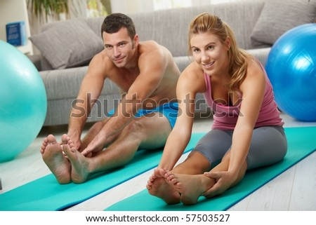 Young couple sitting on fitness mattress and streching legs before treining