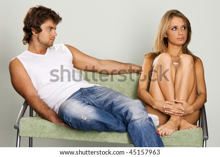 Young couple sitting on green sofa