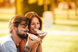 Young couple sitting on park bench and eating pizza.Fast food.