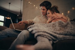 Young couple sitting on sofa at home in winter and using laptop computer. Cozy couple in hygge house with laptop.