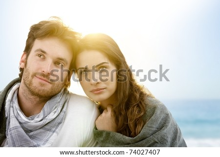 Young couple sitting on summer beach with blanket enjoying sunset.?