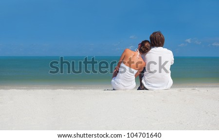 Young couple sitting on the beach looking on the horizon