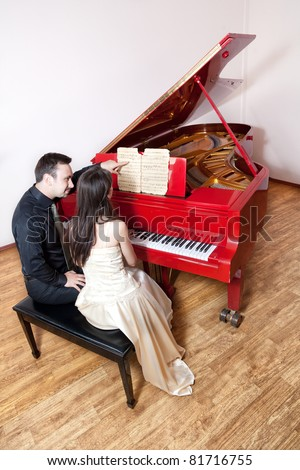 Young couple sitting on the chair near the red grand piano. Serious Man pointing at music sheet and woman looking at it and playing the piano