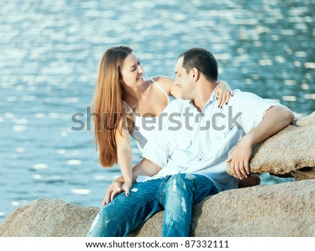 Young couple sitting on the cliff near ocean