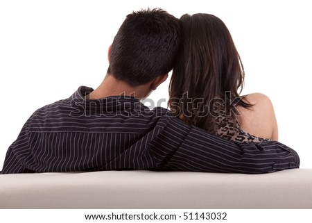 Young couple, sitting on the couch. White background, studio shot.
