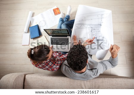 Young couple sitting on the floor and looking at the blueprint of new home.Investment.