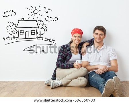Young couple sitting on the floor in a room. #596550983