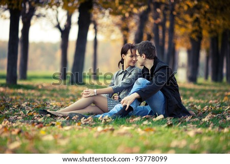 Young couple sitting on the ground in the autumn park