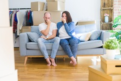 Young couple sitting on the sofa arround cardboard boxes moving to a new house smelling something stinky and disgusting, intolerable smell, holding breath with fingers on nose. Bad smells concept.