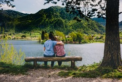 Young couple sitting on wooden bench under a tree at lake in Italy.
