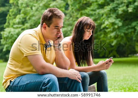 Young couple sitting outdoors on bench bored in relationship