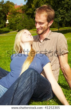 Young couple sitting outside in a park - stock photo