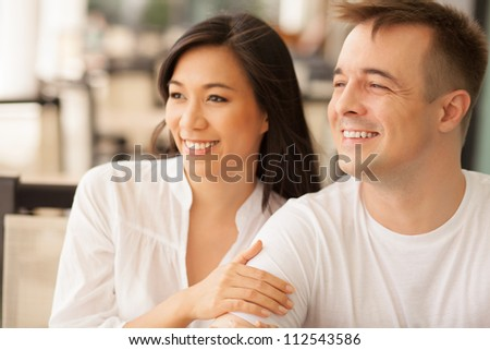 Young couple sitting together and looking away