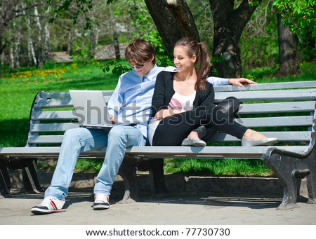 Young couple sitting together on bench in  park and using laptop