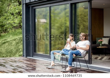 Young couple sitting with cups on the terrace of the modern house enjoying beautiful view outdoors #1108469735