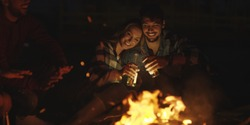 Young Couple Sitting with friends Around Campfire on The Beach At Night drinking beer