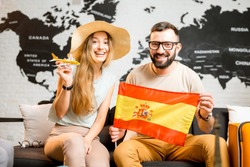 Young couple sitting with spanish flag at the travel agency office on the world map background prepairing for a trip to Spain