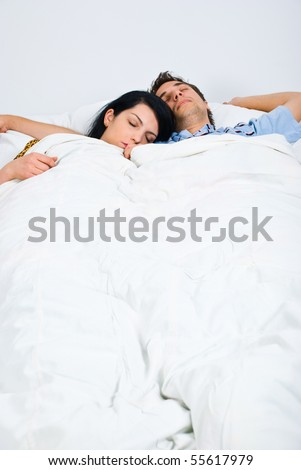 Young couple sleeping on bed  ,woman rest her head on his shoulder