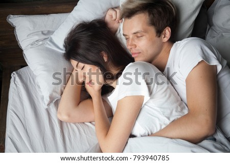Young couple sleeping together embracing cuddling on comfortable bed, loving man hugging beautiful woman lying asleep on soft pillow, enjoying healthy peaceful sleep in bedroom, dozing in the morning