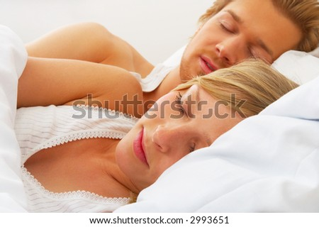 Young couple sleeping together in bed A sensual and cute couple