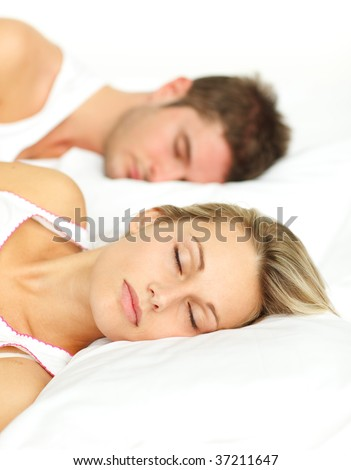 Young couple sleeping together in bed with focus on woman