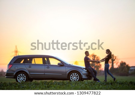 Young couple, slim attractive woman with long ponytail and handsome man standing at silver car in green field on clear sky at sunset or sunrise copy space background.