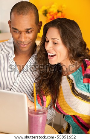 Young couple smile as they work on a laptop.  Vertical shot.