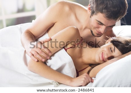 Young couple smiling and hugging on the bed in the bedroom - stock photo