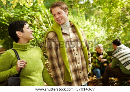 Young couple smiling at each other on forest hiking, with friends in background.?