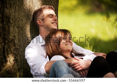 young couple smiling under a tree