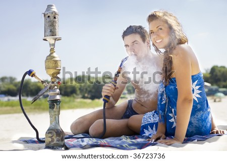 Young couple smoking hookah on the beach