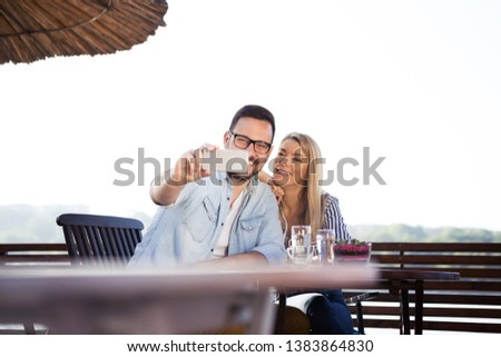 Young couple spend nice moments in a cafe on the river and they want to save this moment and take pictures with a smart phone #1383864830