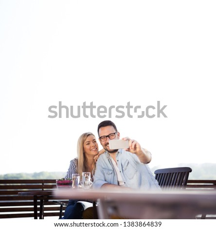 Young couple spend nice moments in a cafe on the river and they want to save this moment and take pictures with a smart phone #1383864839
