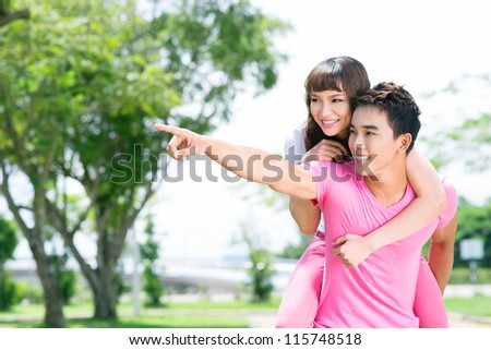 Young couple spending time together, girl pointing at something